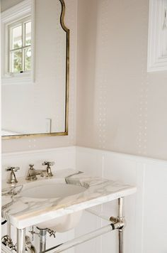 Powder Room . Powder room features upper walls clad in gray Phillip Jeffries Grasscloth and Rivets Wallpaper and lower walls clad in white paneling. #powderroom #wallpaper #PhillipJeffriesGrassclothandRivetsWallpaper