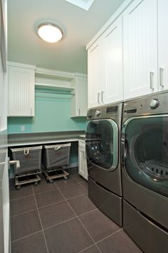 I love the palette of gray, white and turquoise. I want the rolling hampers and storage for my next laundry room! Upper-level laundry rooms are a must-have in today's new homes. Via Homes By Tradition, custom home builder in the Twin Cities, MN