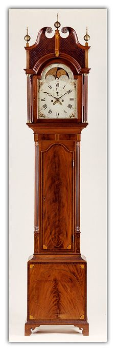 "Federal Inlaid & Figured Mahogany Tall Case Clock having a broken arch top retaining its original carved & gilded ""flower"" rosettes & brass finials above a pierced scroll board & bookend inlays under each outer finial stand & a ""liberty cap on a pole"" inlay under the center finial, an enameled dial with moon phase & date counter, eight day brass movement flanked by fluted colonettes above bookend inlays, straight bracket feet. Case made by Matthew Egerton, New Brunswick, NJ, c1788-1802  H96…"