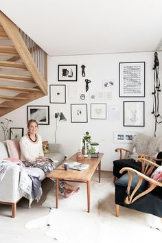 Niki em sua sala com tapete que imita pele e uma manta, itens indispensáveis…