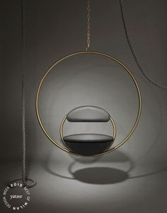 Hanging Hoop Chair by Lee Broom.Suspended from above, two circular brass-plated hoops join to create the Hanging Hoop Chair, with the seat and backrest upholstered in Kvadrat wool.