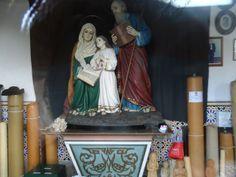 Altar com a Sagrada familia e ao lado ex-votos velas em parafina.