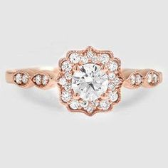 Glittering diamonds and light-catching milgrain form an ornate halo around the center gem in this breathtaking vintage-inspired ring. Pairs of pavé diamonds nestled in marquise-shaped frames gracefully flow down the band for additional sparkle (average Rose Gold Diamond Ring, Diamond Glitter, Rose Gold Glitter, Halo Diamond, Diamond Jewelry, Top Engagement Rings, Vintage Inspired Engagement Rings, Rose Gold Engagement Ring, Engagement Ideas