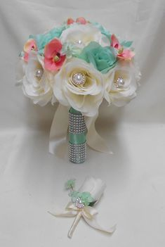 This wedding silk flower package is made with ivory and mint Roses, coral orchids and mint hydrangeas.The ivory roses in the brides bouquet are