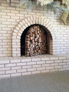 """make paper template of fire box and cut a piece of 3/4"""" plywood to fit inside it snugly, paint plywood black. a few eucalyptus logs from a tree service company and cut them down with a miter saw in random lengths. Liquid Nails to attach them to the black plywood backing."""