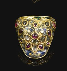 A fine Mughal gem-set and enamelled gold archer's ring, North India, 17th century enamelled with a blue ground and decorated with pink and clear gemstones set in the kundan technique in the form of a flowerhead with foliate stems, the interior with a bright green chevron enamel ground and white and black enamelled flower blossoms.