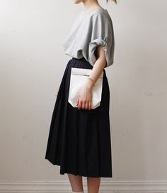 Oversized grey tee tucked into a large pleated skirt and white clutch