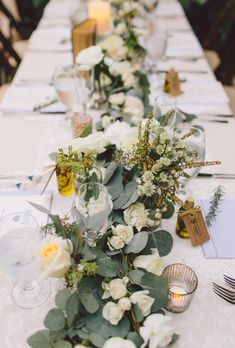 Wedding table with tons of greenery, white roses, and thistle accents