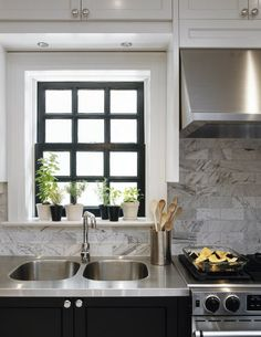 White and gray tile backsplash, dark base cabinets, white wall cabinets, stainless countertops and stainless oven hood.