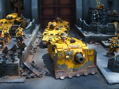 An Imperial Fists Vindicator leads Rhino troop transports from a fortress gate