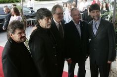 The group Alabama arrives for the Medallion ceremony at the Country Music Hall of Fame May 7, 2006, and are greeted by Director Kyle Young, center. Becoming newest members of the hall are Jeff Cook, left, Randy Owen, Mark Herndon and Teddy Gentry.