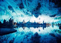 Reed Flute Cave Lake, China  The Reed Flute Cave is a natural limestone cave located in Guilin, Guangxi of China. The cave is over 180 million years old and is covered in historical inscriptions dating back to the Tang Dynasty in 792 AD. Though it was an attraction for thousands of year's prior, it was only rediscovered by a group of refuges in the 1940s. Today, the cave and its multicoloured lake are renowned the world over.