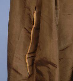 SIMPLE ABITO SETA, c. 1780. 1 pezzo manica lunga verde-marrone con uno stile semplice, retro della gonna con pieghe cucite giù, davanti con coulisse in vita, fondo con due nervature orizzontali, corpetto foderato in lino