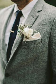 Tweed suit, white shirt, blue tie.