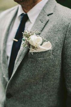 Tweed suit, white shirt, blue tie.