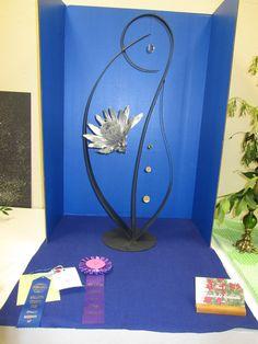 """Moonlight Serenade"" by Susan Andrews. 2010 Standard Flower Show in Bozeman, Montana. Creative Flower Arrangements, Music Symbols, Pomegranates, Metal Structure, Garden Club, Flower Show, Library Ideas, Floral Designs, Ikebana"