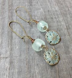 Hand patinated brass sand dollar charm hangs with a sea foam colored recycled glass bead from kidney earwires. Perfect for your summer beach