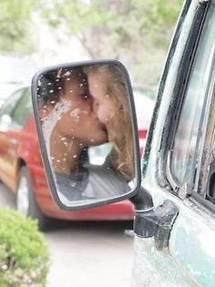 Cute, kiss captured in side mirror