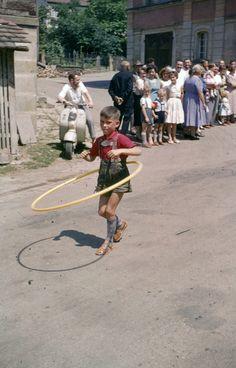 Hula Hoop, ein Mode - Sport, der 1958 aus den USA auch nach Europa überschwappte, war auch beim Kinderfestzug in Walddorf angekommen. Der kleine Junge in Lederhosen scheint den Reifentanz mit Hüftschwung gut zu beherrschen.