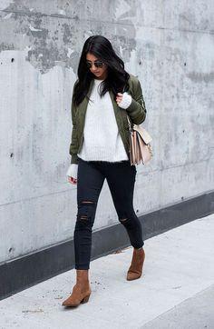 Street style look com calça jeans e suéter branco mais bomber jacket verde e bota marrom bico fino