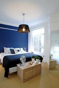 witte muren en dan 1 blauwe muur achter het bed