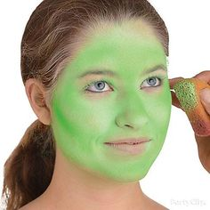 Step 1: Apply green makeup by dabbing on the paint with a sponge. Make sure to blend for the desired green color intensity.