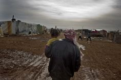 MSF: A Syrian refugee carries his two-year-old daughter in the makeshift and rain-soaked Taybeh refugee camp outside Baalbek in Lebanon's Bekaa Valley, January 18, 2013. Unhygienic conditions in the camp are leading to various communicable illnesses, especially among children. The camp is home to approximately 300 people who fled conflict in Syria. Lebanon 2013 © Michael Goldfarb