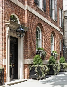 Brick townhouse with arched windows, black shutters, door, and box planters, and an over-door lintel. Sawyer Berson project on East 80th Street.
