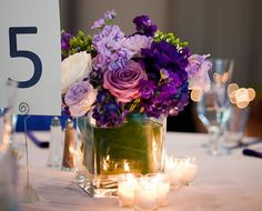 Medium modern sized centerpiece with lavender and white standard roses, lavender and purple stock, lisianthus and green hypericum berry with a submerged banana leaf covering the stems