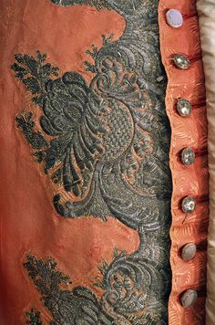 Detail front closure, sleeved waistcoat, fabric: England, garment: America, c. 1759. Flame-orange figured silk with an abstract feather/scroll and leaf design. The dense embroidery consists of silver metallic threads over stiffened paper scroll cut-outs, appliquéd onto the ground fabric, silver buillion embroidery, pailletes and flattened strips decorate the wooden buttons.