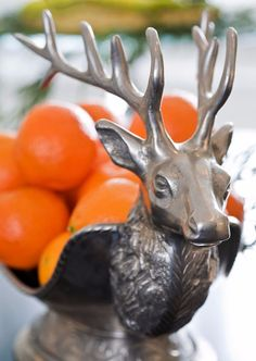 A metal reindeer fruit bowl holding oranges lends a subtle holiday touch to the counter space. - Traditional Home® / Photo: Gordon Beall