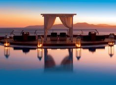 View of the Aegean sea as seen from the Pool Area of the Mykonos Grand Luxury Hotel & Resort while the summer sun is setting. The sky has a combination of blue and orange hues producing a dreamy feeling.