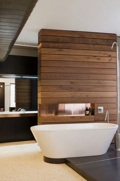 Rustic wood divider wall in bathroom is quite nice with white fixtures, dark…