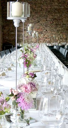 Tischdekoration für Hochzeit im Vintage Loog mit hohen Kerzenleuchtern und Blumendeko in rosa und weiss