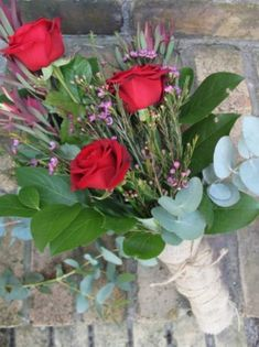 An elegant wrap of red Naomi Roses and seasonal foliage, tied with Hessian.