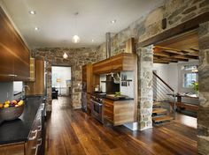 Farmhouse kitchen. Love the exposed stone walls and those gorgeous wood floors