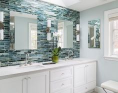 counter to ceiling blue tile, frameless mirrors, sconces