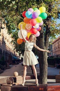 Mujer joven feliz con globos de látex de colores manteniendo su vestido, escena urbana, al aire libre Foto de archivo - 15785729