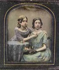 Antique Victorian tinted photo of two pretty little girls with ringlets and roses.
