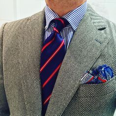 Light grey tweed jacket, white shirt with blue dress stripes, blue tie with red & white stripes