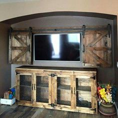 Rustic home design idea. Brilliant idea for the TV with swinging barn like doors.