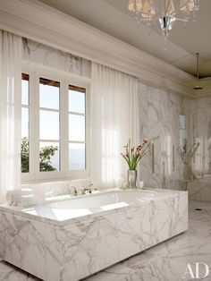 The master bath of this Napa, California, home decorated by the Wiseman Group features marble from Walker Zanger, Kallista bath fittings, and a Murano Nevada chandelier by Barovier & Toso.