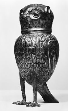 Cup of silver, parcel gilt in form of an owl embossed and chased made in Germany (17th century). Owl stands very erect, tail a quadrangular plate serving as third foot; removable head serves as cup.  Rim beneath engraved with scrolls; feathers embossed in even horizontal rows, plain and gilt, in diagonal lines.