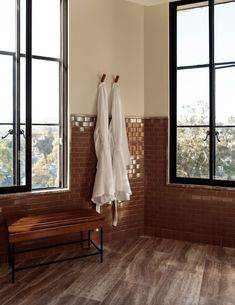 The luxury hotel aesthetic of Santa Monica Proper features a neutral palette and organic textures reminiscent of California. This spacious travertine bathroom features architectural sconce lighting and travertine walk-in showers. Tap the pin for more bathroom, hotel design and bathroom remodel ideas.