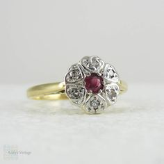 (http://www.addysvintage.co.uk/art-deco-ruby-diamond-cluster-ring-daisy-shaped-1920s-platinum-top-yellow-gold-engagement-ring/)
