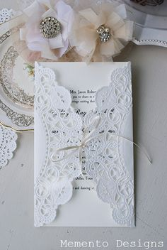 Wrap a Doile around the Invitation & tie it with ribbon! This would actually be affordable! And a great idea!