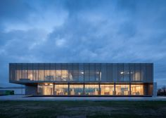 Factory building in Belgium comprising solid concrete, metal mesh and glass surfaces.