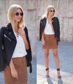 Lederjacke, brauner Wildlederrock , weiße Bluse und eine große Sonnenbrille. Mit diesen einfachen Basics lässt sich ein cooler Herbstlook kreieren.
