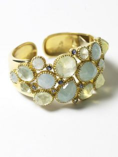 A gorgeous cuff made of 18c yellow gold.  The stones are a combination of semi precious iolite, milky aquamarines, green calcedony.