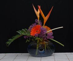 Lilacs, psittacorum heliconia, gerbera and Xanadu foliage from Rittners Floral School, Boston, MA www.floralschool.comwww.floralschool.com